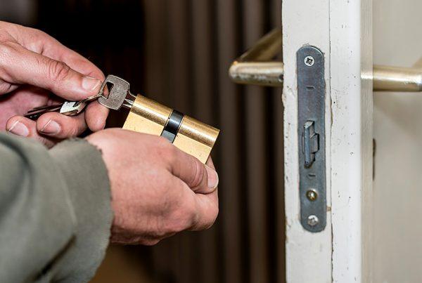 Cerrajería instalando cerradura en la puerta residencial